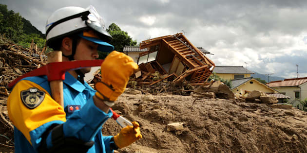HIROSHIMA, JAPAN - AUGUST 21:  Rescue teams continue the search for missing people among the debris of houses destroyed by a landslide caused by torrential rain at the site of a landslide in a residential area on August 21, 2014 in Hiroshima, Japan. Rescue work continues as at least 39 people were confirmed dead and 7 people are missing one day after the torrential rain caused flooding and landslides in the city of Hiroshima early Wednesday August 20, 2014.  (Photo by Buddhika Weerasinghe/Getty Images)