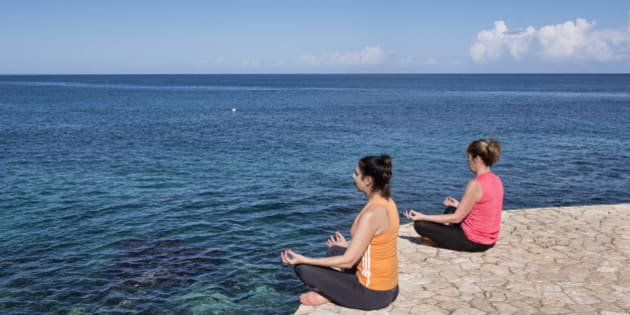 NEGRIL, WEST END, WESTMORELAND PARISH, JAMAICA - 2014/01/10: Two women practice yoga from a waterfront ledge. (Photo by John Greim/LightRocket via Getty Images)
