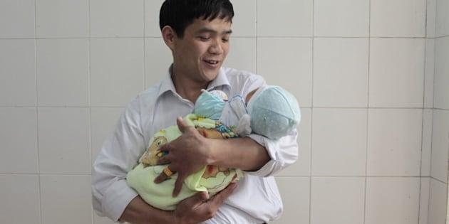 CAO BANG CITY, CAO BANG, VIETNAM - 2011/04/25: A father with his new born baby in Cao Bang provincial hospital. The World Health Report 2005 Ð Make Every Mother and Child Count, says that in that year almost 11 million children under five years of age will die from causes that are largely preventable. Among them are 4 million babies who will not survive the first month of life. At the same time, more than half a million women will die in pregnancy, childbirth or soon after. The report says that reducing this toll in line with the Millennium Development Goals depends largely on every mother and every child having the right to access to health care from pregnancy through childbirth, the neonatal period and childhood. new born, baby, mother, father, family, breast feeding, hostpital. (Photo by Chau Doan/LightRocket via Getty Images)