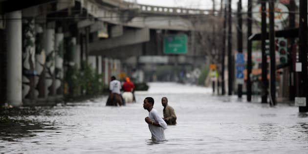 New Orleans residents walk through chest deep floodwater after Hurricane Katrina made landfall on the Louisiana coast on Monday, Aug. 29, 2005. (AP Photo/Dave Martin)