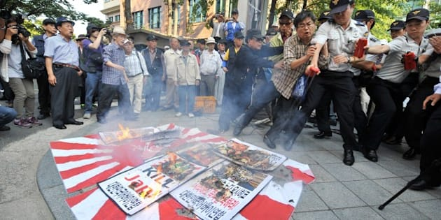 South Korean protestors burn a Japanese rising-sun flag and placards during an anti-Japanese rally over South Korean comfort women, outside the Japanese embassy in Seoul on September 24, 2012. Japan should resolve a long-standing grievance regarding Korean women forced to serve as sex slaves during World War II through a sincere apology and compensation, a senior Seoul official said on September 24, 2012, refuting published remarks on the matter by Japanese Prime Minister Yoshihiko Noda.  AFP PHOTO/JUNG YEON-JE        (Photo credit should read JUNG YEON-JE/AFP/GettyImages)