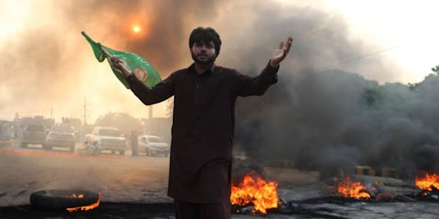 LAHORE, PAKISTAN - AUGUST 31: A supporter of the Pakistan Tehreek-e-Insaf (PTI) political party waves flag as they block the road with burning tires in Lahore, Pakistan on August 31, 2014. At least 4 people killed and more than 500 wounded in clashes between thousands of police and protesters in Pakistan's capital Islamabad Saturday, as a fortnight-long political impasse took a violent turn when opposition groups attempted to storm the prime minister's residence. (Photo by Rana Irfan Ali/Anadolu Agency/Getty Images)