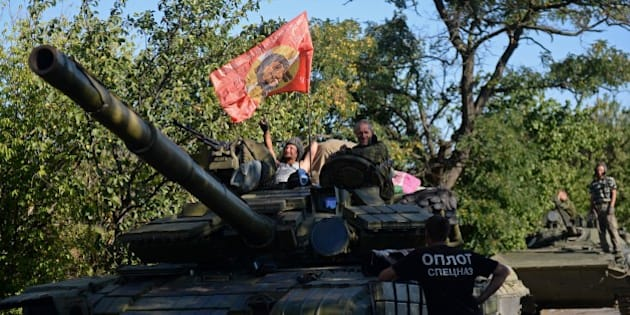 Pro-Russian fighters sit ontop of a tank in Starobesheve, southeast of Donetsk, on August 31, 2014. Pro-Russian separatists were preparing a fresh offensive on a key coastal location in eastern Ukraine on Sunday, as EU leaders gave Moscow one week to curb its support for the rebels or face new sanctions. A ragtag mix of volunteer battalions and local residents were bracing for a desperate defence of Mariupol, a strategic port city and the last big town in the region still under Ukrainian control. AFP PHOTO / FRANCISCO LEONG        (Photo credit should read FRANCISCO LEONG/AFP/Getty Images)