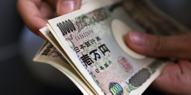 A woman counts Japanese 10,000 yen notes in this arranged photograph taken in Tokyo, Japan, on Friday, Dec. 13, 2013. The yen fell to a five-year low versus the dollar as the difference in yield between Treasuries and Japanese bonds approached the widest level since April 2011. Photographer: Tomohiro Ohsumi/Bloomberg via Getty Images