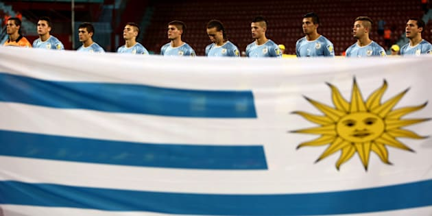Players of Uruguay listen to their national anthem as they stand next to their national flag prior to their Semi-Final football match against Iraq at the FIFA Under 20 World Cup at Huseyin Avni Aker stadium in Trabzon on July 10, 2013. AFP PHOTO/BEHROUZ MEHRI +++ RESTRICTED TO EDITORIAL USE +++        (Photo credit should read BEHROUZ MEHRI/AFP/Getty Images)