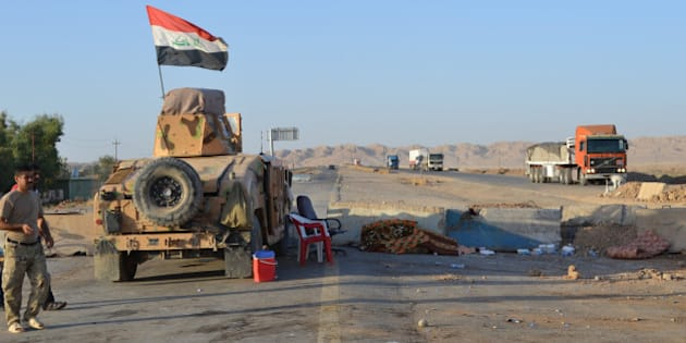SALADIN, IRAQ - SEPTEMBER 07: Lorries and a tank are on the Kirkuk - Baghdad road in Suleiman Bey, town of Tuz Khurmato, Iraq, on September 7, 2014. The road from Kirkuk to Baghdad has reopened after being closed three months following some regions being captured by the Islamic State of Iraq and the Levant (ISIL). Checkpoints have now been set up along the road by the Iraqi armed forces and Peshmerga forces. (Photo by Adem Demir/Anadolu Agency/Getty Images)