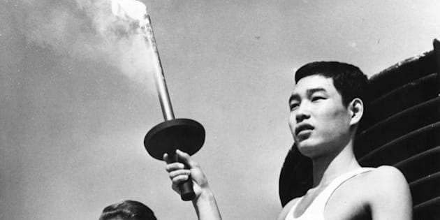 5th October 1964:  Yoshinori Sakai, born at Hiroshima on the day the first atomic bomb was dropped on the city, holding the Olympic torch beside Greek actress Aleka Katseli during a rehearsal for the opening of the Olympic Games at Tokyo.  (Photo by Central Press/Getty Images)