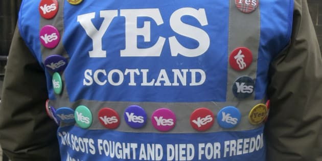 """In this photo taken March 15, 2014 a man wears a multitude of 'yes' campaign badges during a pro-independence march in Edinburgh, Scotland for the upcoming vote on Scotland's independence from the United Kingdom. Scotland's swithering """"middle million"""" has Britain's future in its hands. """"Swithering"""" means wavering, and it's a word you hear a lot in Scotland right now. Six months from Tuesday, Scottish voters must decide whether their country should become independent, breaking up Great Britain as it has existed for 300 years. Faced with the historic choice, many find their hearts say """"aye"""" but their heads say """"why risk it?"""" Polls suggest as many as a quarter of Scotland's 4 million voters remain undecided, and their choice will determine the outcome. Many long to cut the tie binding them to England, but fear the risks _ and the financial fallout. (AP Photo/Jill Lawless)"""
