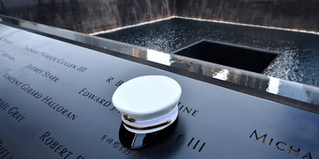 A firefighter's hat sits on names of  firefighters who died at the South Pool, during anniversary ceremonies at the site of the World Trade Center on September 11, 2012 in New York.        (Photo credit should read JUSTIN LANE/AFP/GettyImages)