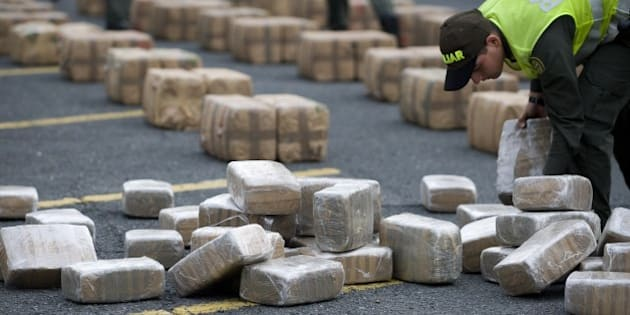 A Colombian anti-drugs police officer checks packages of marijuana, part of a load of five tons seized in the outskirts of Cali, department of Valle del Cauca, Colombia, on February 27, 2012.  AFP PHOTO/Luis ROBAYO (Photo credit should read LUIS ROBAYO/AFP/Getty Images)