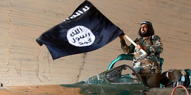 This undated image posted on Wednesday, Aug. 27, 2014 by the Raqqa Media Center of the Islamic State group, a Syrian opposition group, which has been verified and is consistent with other AP reporting, shows a fighter of the Islamic State group waving their flag from inside a captured government fighter jet following the battle for the Tabqa air base, in Raqqa, Syria on Sunday.   A U.N. commission on Wednesday accused the extremist Islamic State organization of committing crimes against humanity with attacks on civilians, as pictures emerged of the extremists' bloody takeover of a Syrian military air base that added to the international organization's claims.  (AP Photo/ Raqqa Media Center of the Islamic State group)