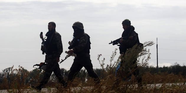 Ukrainian soldiers walk at a checkpoint controlled by Ukrainian forces on September 10, 2014, near the small eastern Ukrainian city of Slavyanoserbsk, in the Lugansk region. German Chancellor Angela Merkel called on September 10 for the European Union to move quickly on new sanctions against Russia, saying they could always be lifted if a Ukraine ceasefire holds. Ukrainian President Petro Poroshenko said on September 10 that Russia had withdrawn most of the troops it allegedly snuck across the border to bolster pro-Kremlin rebels, and vowed greater autonomy for the separatist east in order to sustain a fragile new truce. AFP PHOTO/ ANATOLII STEPANOV        (Photo credit should read ANATOLII STEPANOV/AFP/Getty Images)