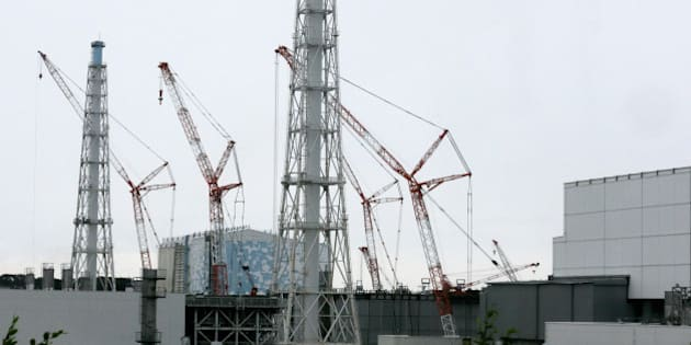 Cranes operate at Unit 3, center, standing next to Unit 4, right, at Tokyo Electric Power Co.'s (Tepco) Fukushima Dai-ichi nuclear power plant in Okuma, Fukushima Prefecture, Japan, on Wednesday, July 9, 2014. All of Japan's 48 operable commercial reactors are idled for safety assessments after the accident at the Fukushima plant. Photographer: Kimimasa Mayama/Pool via Bloomberg