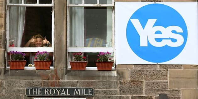 File photo dated 09/09/14 of a woman giving the thumbs up from a window in a property next to a YES sign on the Royal Mile in Edinburgh. Campaigning on both sides continues with only a week to go before Scotland decides on independence.