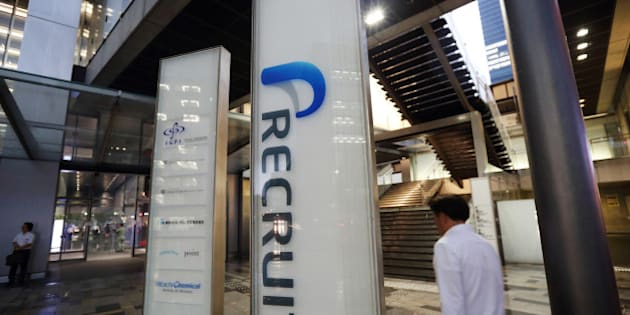 A man holding an umbrella walks past signage for Recruit Holdings Co. outside the building housing the company's head office in Tokyo, Japan, on Wednesday, Sept. 10, 2014. Recruit, a Japanese provider of staffing services, plans to raise about 178 billion yen ($1.7 billion) in an initial public offering next month to expand through acquisitions and investments. Photographer: Tomohiro Ohsumi/Bloomberg via Getty Images