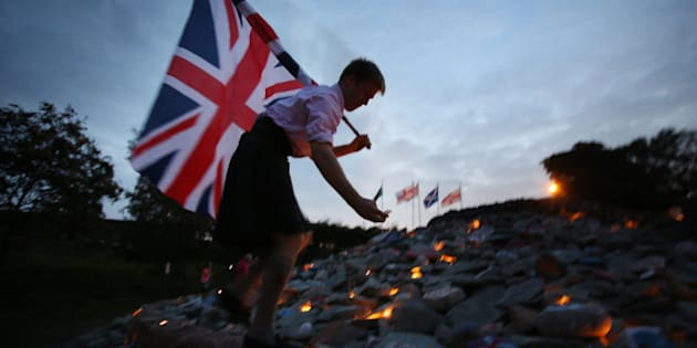 GRETNA GREEN, SCOTLAND - SEPTEMBER 16:  Better Together campaigner Monty Lewis holds a Union flag as he lights candles on a cairn near the Scotland England border on September 16, 2014 in Gretna, Scotland. Yes and No supporters are campaigning in the last two days of the referendum to decide if Scotland will become an indpendent country.  (Photo by Peter Macdiarmid/Getty Images)