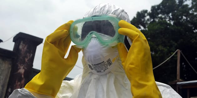 CONAKRY, GUINEA - SEPTEMBER 13:  A member of a volunteer medical team wears protective glasses before burying the body of an Ebola victim died due to the Ebola virus, in the capital Conakry, Guinea on September 13, 2014. (Photo by Mamadou Cellou Diallo/Anadolu Agency/Getty Images)