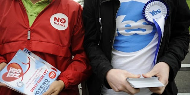 Pro-independence (R) and pro-union campaigners are pictured outside a polling station in east Glasgow, Scotland, on September 18, 2014, during a referendum on Scotland's independence. Scotland began voting Thursday on whether to become independent, in a referendum that could break up the centuries-old United Kingdom and create Europe's newest country since the collapse of Yugoslavia.  AFP PHOTO / ANDY BUCHANAN        (Photo credit should read Andy Buchanan/AFP/Getty Images)