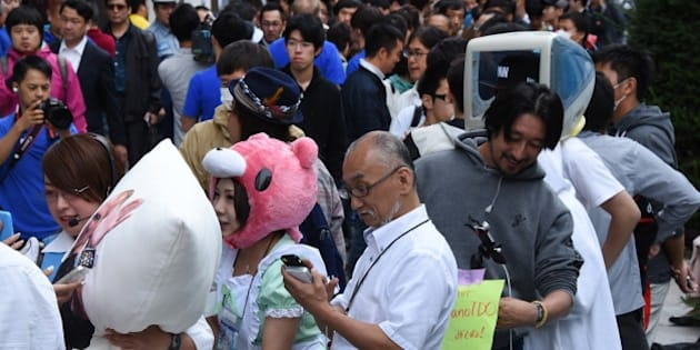People wait for the release of the iPhone 6 in front of an Apple store in the Ginza shopping district in Tokyo on September 19, 2014. Apple's new smartphone iPhone 6 was released in Japan on September 19.     AFP PHOTO/Toru YAMANAKA        (Photo credit should read TORU YAMANAKA/AFP/Getty Images)