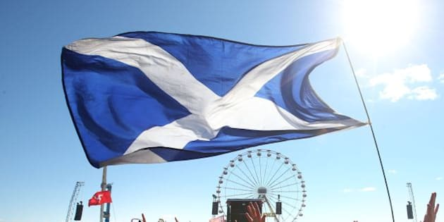 Music fans with a Saltire Flag in front of the Main Stage at the T in the Park music festival held at Balado Park in Kinross, Scotland.