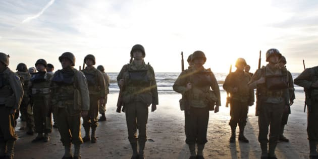 A group of military enthusiasts stand on Omaha Beach in Vierville sur Mer, western France , Friday June 6, 2014. World leaders and dignitaries including President Barack Obama and Queen Elizabeth II will gather to honor the more than 150,000 American, British, Canadian and other Allied D-Day troops who risked and gave their lives to defeat Adolf Hitler's Third Reich. (AP Photo/Thibault Camus)