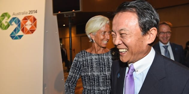 Head of the IMF Christine Lagarde (C) greets Japan's Minister of Finance Taro Aso (R) at the G20 Finance Ministers and Central Bank Governors Meeting in Cairns on September 20, 2014.   Finance ministers from G20 nations meet in Cairns this weekend as they grapple with how to achieve a lift in global growth by two percent while being held back by a sickly eurozone recovery. AFP PHOTO/William WEST        (Photo credit should read WILLIAM WEST/AFP/Getty Images)