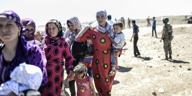 Syrian Kurd families carry their belongings after they crossed the border between Syria and Turkey near the southeastern town of Suruc in Sanliurfa province, on September 20, 2014. Several thousand Syrian Kurds began crossing into Turkey on September 19 fleeing Islamic State fighters who advanced into their villages, prompting warnings of massacres from Kurdish leaders. Turkey on September 19 reopened its border with Syria to Kurds fleeing Islamic State (IS) militants, saying a 'worst-case scenario' could drive as many as 100,000 more refugees into the country. AFP PHOTO/BULENT KILIC        (Photo credit should read BULENT KILIC/AFP/Getty Images)