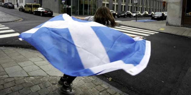 A young girl runs around a street pole with a Scottish national flag before taking part in a demonstration in favor of Scottish independence in Brussels on Thursday, Sept. 18, 2014. Scots held the fate of the United Kingdom in their hands Thursday as they voted in a referendum on becoming an independent state, deciding whether to unravel a marriage with England that built an empire but has increasingly been felt by many Scots as stifling and one-sided. (AP Photo/Virginia Mayo)