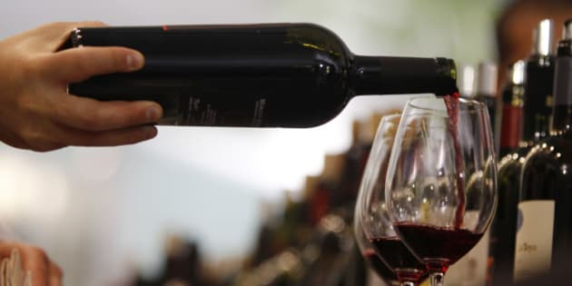 """A man pours a glass of red wine on the opening day of the 44th edition of the annual International Wine and Spirits Exhibition """"Vinitaly"""", in Verona, northern Italy, Thursday, April 8, 2010. The wine exhibition runs until April 12. (AP Photo/Luca Bruno)"""