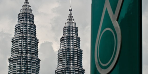 Malaysia's iconic Twin Towers are seen in the background of the Malaysian oil and gas company Petronas logo at a petrol station in Kuala Lumpur on August 13, 2014. Malaysian state energy firm Petronas is expected to announce its second quarter earnings later on August 13.   AFP PHOTO / MANAN VATSYAYANA        (Photo credit should read MANAN VATSYAYANA/AFP/Getty Images)