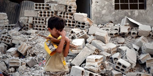 DAMASCUS, SYRIA - SEPTEMBER 24:  A Syrian boy walks next the rubble of a collapsed building following the Syrian army's airstrikes on the opposition controlled Duma district, in the suburbs of Damascus, Syria on September 24, 2014. (Photo by Yousef Albostany/Anadolu Agency/Getty Images)