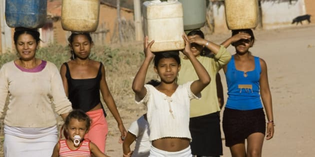 Women balance water jugs on their heads in one of Guaribas' hamlet, in Brazil's northeastern state of Piaui, Wednesday, Aug. 23, 2006.  Although they don't have running water, now some of the hamlets have communal cisterns that are centrally located. (AP Photo/Victor R. Caivano)
