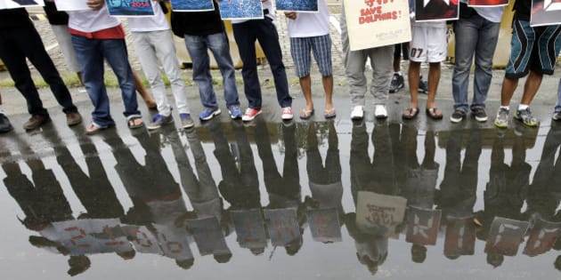 """Environmental activists form the phrase """"Stop The Killings"""" outside the Japanese Embassy Monday, Sept. 1, 2014 at suburban Pasay city south of Manila, Philippines, to protest the annual hunting of dolphins in Taiji, Japan which starts on the first day of September. In their statement, the Filipino  environmentalists are joining other activists around the globe in """"exposing and opposing this cruel and inhumane activity."""" (AP Photo/Bullit Marquez)"""