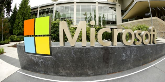 This photo taken with a fisheye lens on July 3, 2014 shows Microsoft Corp. signage outside the Microsoft Visitor Center in Redmond, Wash. Microsoft on Thursday, July 17, 2014 announced it will lay off up to 18,000 workers over the next year.  (AP Photo Ted S. Warren)
