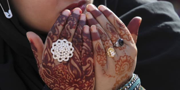 "A Pakistani worshipper wearing henna designs on her hands prays at the Badshahi Mosque on the first day of the Muslim holiday of Eid al-Adha, or ""Feast of Sacrifice,"" in Lahore, Pakistan, Wednesday, Oct. 16, 2013. (AP Photo/K.M. Chaudary)"