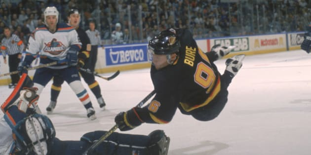 Russian hockey player Pavel Bure of the Vancouver Canucks sails through the air as he tries to score on the New York Islanders goalie, Uniondale, New York, 1995-96 season (Photo by Bruce Bennett Studios/Getty Images)