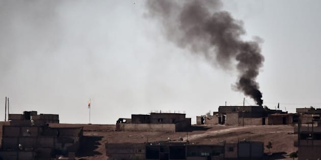 Smoke rises from the central part of the Syrian town of Ain al-Arab, known as Kobane by the Kurds, as seen from the Turkish-Syrian border, as a Kurdish flag waves during heavy fighting, in the southeastern town of Suruc, Sanliurfa province, on October 7, 2014. Pro-Kurdish protesters clashed overnight on October 7 with police in several Turkish cities, including Istanbul, in a show of anger against the lack of action by the government against jihadists fighting for a key Syrian town.