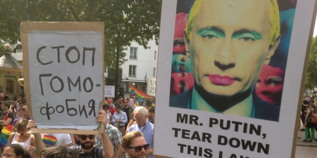 """A demonstrator holds a poster with the portrait of Russian President Vladimir Putin during a protest march against the new Russian gay law, in Berlin, Germany Saturday, Aug. 31, 2013.  The new law penalizes anyone who distributes information aimed at persuading minors that """"nontraditional"""" relationships are normal or attractive. Poster at left reads """"Stop Homophobia"""". (AP Photo/Gero Breloer)"""