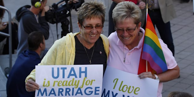 SALT LAKE CITY, UT - OCTOBER 6: People hold signs and cheer at a same-sex marriage victory celebration on October 6, 2014 at the Salt Lake City Library in Salt Lake City, Utah. Partridge was one of the plaintiffs in the case today where the U.S. Supreme Court declined to take up challenges to same-sex marriage making it legal now in Utah. (Photo by George Frey/Getty Images)