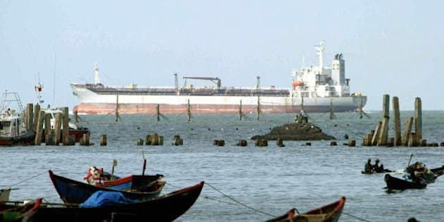 VUNG TAU, VIET NAM:  A oil tanker ship sails past a fishing port in Southern coastal city of Vung Tau, 18 November 2003.  Vung tau is Vietnam's centre for petrol and gaz industries, which revenues contribute significantly to the national budget.  AFP PHOTO/HOANG DINH NAM/na.  (Photo credit should read HOANG DINH NAM/AFP/Getty Images)