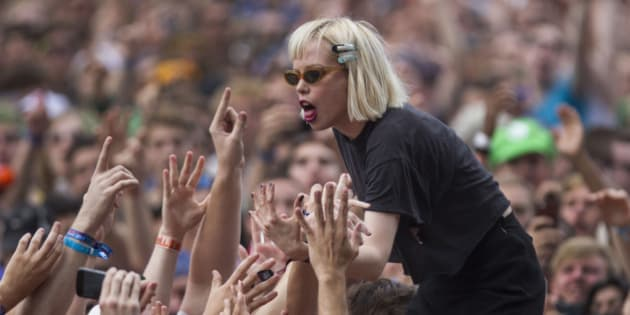 Alice Glass, vocalist for Canadian electronic band Crystal Castles interacts with fans after jumping off stage during their performance at the Lollapalooza Festival in Chicago, Friday, Aug. 2, 2013. (AP Photo/Scott Eisen)