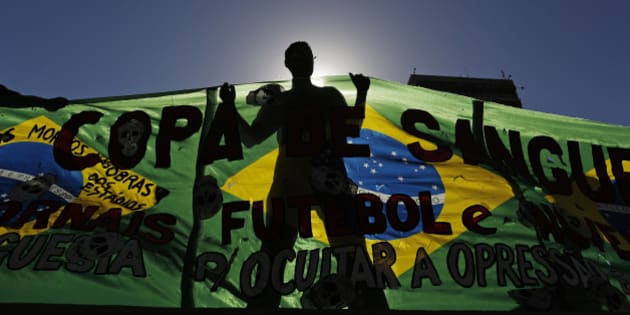 An Anti-World Cup demonstrator holds a banner during a protest near Maracana stadium on the last day of the World Cup soccer tournament in Rio de Janeiro, Brazil, Sunday, July 13, 2014. Protesters criticize that the government should spend money on improvements for education, health and housing, instead of soccer. (AP Photo/Leo Correa)