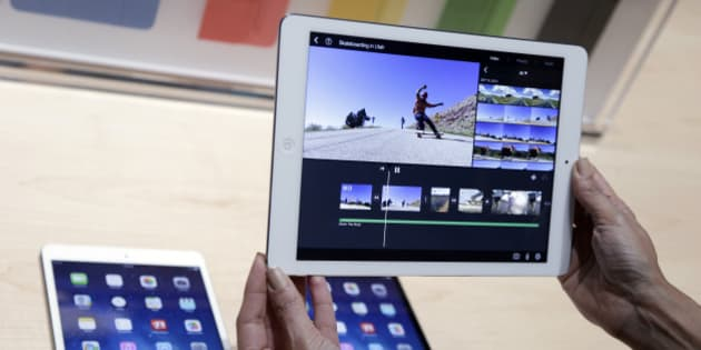 "An Apple employee holds up the new iPad Air on Tuesday, Oct. 22, 2013, in San Francisco. Apple unveiled a new, thinner, lighter tablet called the ""iPad Air"" along with a slew of new Macs Tuesday at an event in San Francisco. The iPad Air weighs just 1 pound, compared with 1.4 pounds for the previous version. (AP Photo/Marcio Jose Sanchez)"