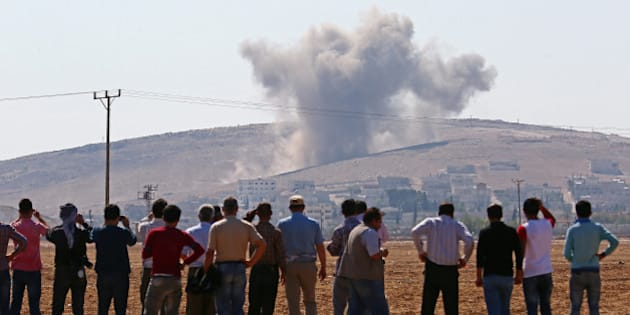 SANLIURFA, TURKEY - OCTOBER 08: A photograph taken from Suruc district of Sanliurfa, Turkey, shows that local residents watch smoke rising from the Syrian border town of Kobani (Ayn al-Arab) following the US-led coalition airstrikes against the Islamic State of Iraq and the Levant (ISIL) on October 8, 2014. (Photo by Emin Menguarslan/Anadolu Agency/Getty Images)