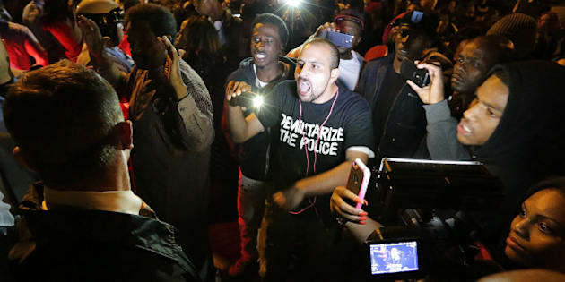 Bassem Masri, center, a man who has live streamed many of the protests in Ferguson, Mo., confronts a St. Louis police officer at the intersection of Shaw Boulevard and Klemm Street as protesters gathered at the scene of a fatal police officer-involved shooting on Wednesday, Oct. 8, 2014. (David Carson/St. Louis Post-Dispatch/MCT via Getty Images)