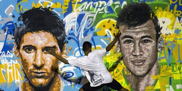 Youngsters play football in front of a mural of Argentine football player Lionel Messi (L) and Brazil's player Neymar da Silva Santos Junior at a field of Tavares Bastos shantytown (favela) in Rio de Janeiro, Brazil on June 8, 2014, just four days ahead of the FIFA World Cup 2014.  AFP PHOTO / YASUYOSHI CHIBA        (Photo credit should read YASUYOSHI CHIBA/AFP/Getty Images)