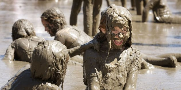 ESTLAND, MI - JULY 7:  Kelli Yokom (left), 13, of Redford, Michigan and her friend Stephanie Janssen (right), 9, also of Redford, play with hundreds of other children in a giant lake of mud at the annual Mud Day event July 7, 2009 in Westland, Michigan. The event is sponsored by the Wayne County Parks and Recreation Department and the mud hole is made with approximately 200 tons of topsoil and 20,000 gallons of water. (Photo by Bill Pugliano/Getty Images)