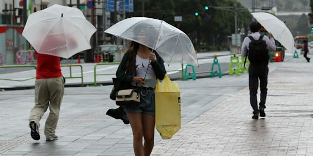 HIMEJI, JAPAN - OCTOBER 13:  Pedestrians walk in the wind and rain delivered by Typhoon Vongfong on October 13, 2014 in Himeji, Japan. According to the Japan Meteorological Agency (JMA), Vongfong surpassed Genevieve for the most intense western Pacific typhoon of 2014 by estimated central pressure of 970 hectopascals at its center and packing winds of up to 180 kilometers per hour. Local media reported at least 44 people were injured in typhoon-related accidents, while Japanese airlines cancelled at least 329 flights. JMA has issued the high aleart for heavy rainfall as well as strong winds and waves. Over 80 people deaths following three previous typhoons and torrential rain in Japan this year  (Photo by Buddhika Weerasinghe/Getty Images)