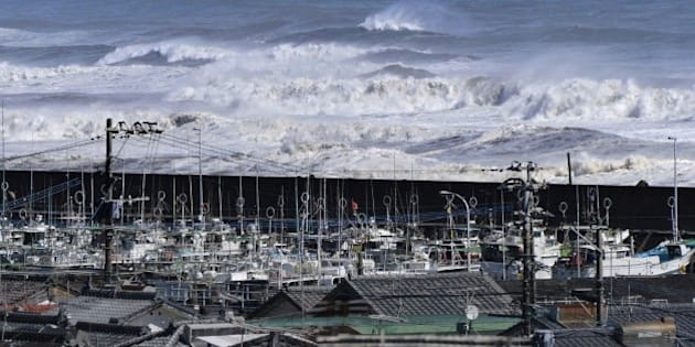 High waves surge toward a port of Kawaminami town in Miyazaki prefecture, Japan's southern island of Kyushu on October 13, 2014, while fishing boats evacuate in the port. Powerful typhoon Vongfong barreled into Japan, with at least one person missing and dozens injured. AFP PHOTO / JIJI PRESS    JAPAN OUT        (Photo credit should read JIJI PRESS/AFP/Getty Images)