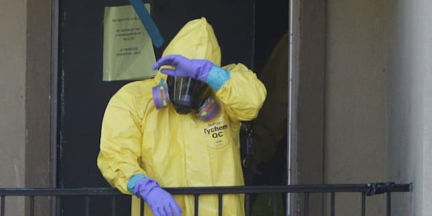 A hazardous material cleaner talks a break from cleaning the apartment where Thomas Eric Duncan, the Ebola patient who traveled from Liberia to Dallas, stayed last week, in Dallas, Monday, Oct. 6, 2014. Duncan has been hospitalized at Texas Health Presbyterian Hospital since Sept. 28. (AP Photo/LM Otero)